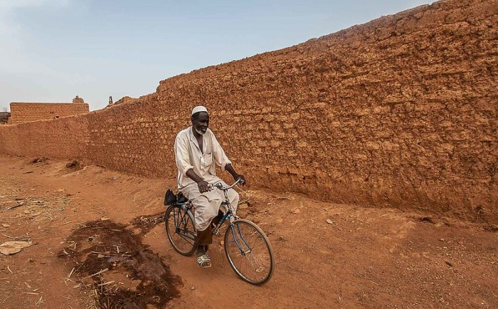 man on a bicycle in front the great mud mosque in the bani in northern Burkina Faso, Sahel