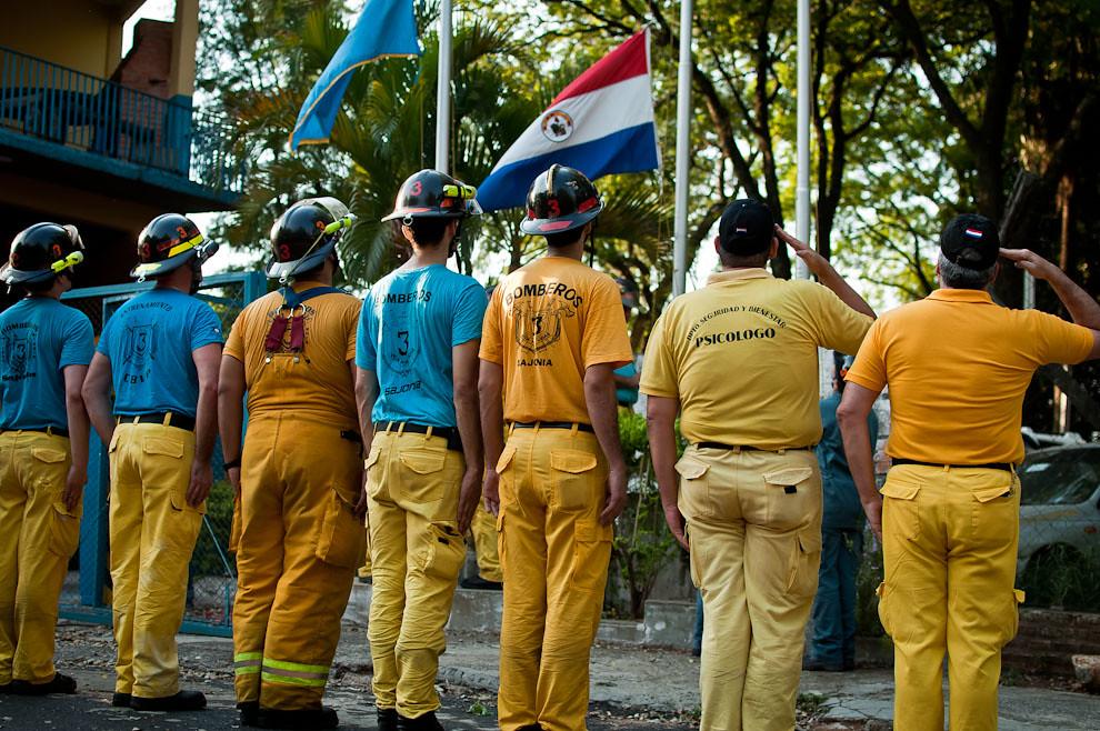 Los bomberos saludan a la bandera paraguaya y a la bandera de la compañía mientras las arrían del mástil, durante el término del entrenamiendo de los sábados en la sede de la 3ra. compañía de Sajonia. A pesar de estar cansados y transpirados, el espíritu de los bomberos sigue fuerte. Esta clase de actitud es digna de admirar: el amor a la patria, el valor, la disciplina y la abnegación son cualidades requeridas para reunir a verdaderos héroes. (Elton Núñez).