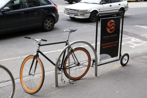 Bike with an advertising trailer, chained up to a bike rack