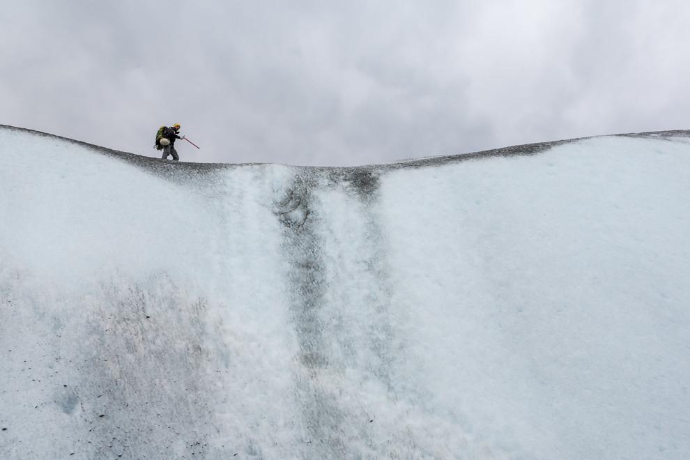 Un guía del equipo Viedma Pro, camina sobre una pared de hielo, para instalar diversos equipos que le permitirán escalar la pared a los turistas que realizan el trekking. (Tetsu Espósito).