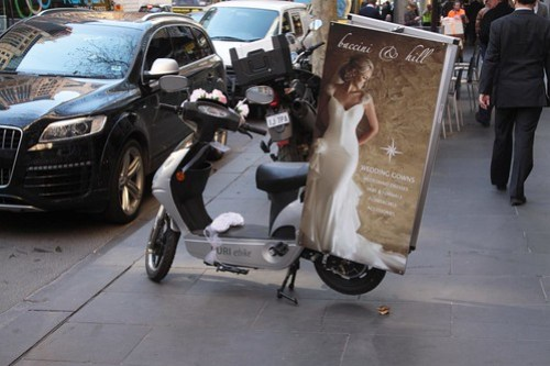 Wedding gown advertising tied to a parked electric bike on Collins Street