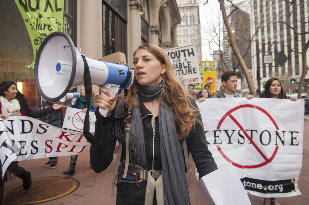 Valerie Love leads a march on Market Street in downtown San Francisco to the State Department building where other demonstrators occupied the lobby and risked arrest Monday, March 1. Photo by Jessica Christian / Xpress