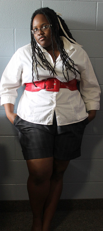 black female with dreads wearing a white blouse, red belt, and black patterened shorts