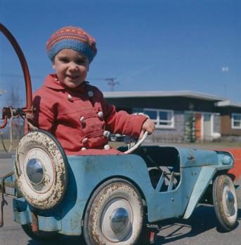 Young child wearing knitted cap, driving toy car / Jeune enfant portant un bonnet de laine et conduisant une voiture jouet