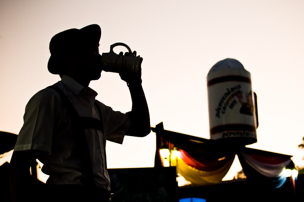 Un joven de Colonia Independencia, termina de beber su vaso de cerveza frente al portal de bienvenida al Club Alemán que sostiene una enorme escultura en forma de manija de Chopp. Estilo que se está repitiendo en cada año. (Elton Núñez)
