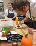 Carefully plating Braised Lamb at the Culinary Capers station