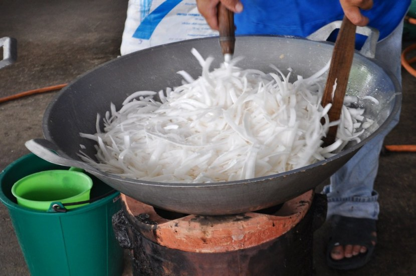 Thin slices of coconut is cooked in boiling water and sugar in Chiang Khan, Loei, Thailand.