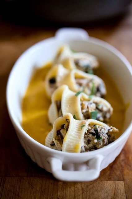 A delicious recipe for stuffed shells with pumpkin sauce, with Italian sausage (or substitute mushrooms) and a creamy flavorful Pumpkin parmesan sauce. | www.feastingathome.com