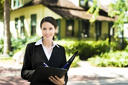Young Businesswoman Real Estate Agent in Front of Home