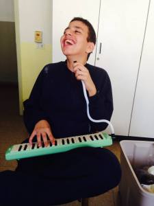 Student at Blessed learning to play the Melodica