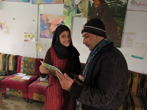 Syrian teen showing her artwork to an instructor in an art therapy program at a refugee camp in the Akkar district, Lebanon