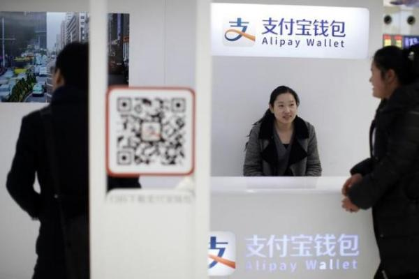 Sales assistant sits behind and under Alipay logos at a train station in Shanghai