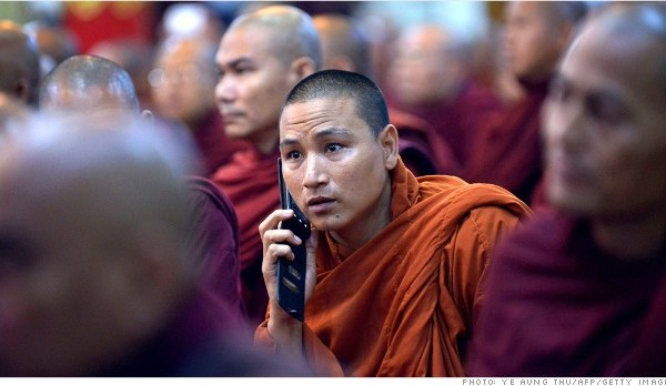 A monk talks on his mobile phone during a meeting of Buddhist monks at a monastery outside Yangon on June 27, 2013.  Myanmar was due to reveal winners of two licences to provide mobile coverage in a country where less than 10 percent of the population has access to a telephone.   AFP PHOTO / Ye Aung THU        (Photo credit should read Ye Aung Thu/AFP/Getty Images)