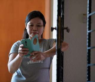 Filipino maid Nilda Sesaldo bought SMS codes through online portal BeamAndGo, which her teenage daughter used to redeem vouchers for groceries at the supermarket and a new phone at a local shop.ST PHOTO: DESMOND FOO