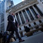 A man walks past the New York Stock Exchange (NYSE) in New York, U.S., on Friday, March 18, 2016. Shares in developing nations are poised to enter a bull market and the Standard & Poors 500 Index erased this years losses as gains in oil and favorable shifts in central-bank policies support riskier assets. Photographer: Michael Nagle/Bloomberg