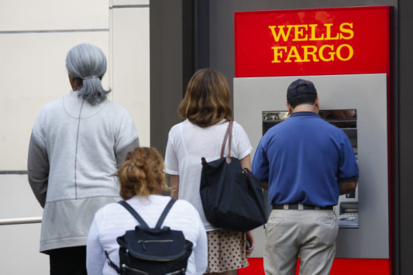 Customers wait in line for an ATM outside of a Wells Fargo & Co. bank branch in Los Angeles, California, U.S., on Tuesday, July 7, 2015. Wells Fargo & Co. is scheduled to report quarterly earnings on July 14. Photographer: Patrick T. Fallon/Bloomberg via Getty Images
