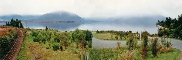 Panoramic view of a brooding Lake Brunner with low cloud covering the top of Mt Te Kinga in the distance to the left of center. The Arnold River flows out of Lake Brunner at the right of picture. Trains carry West Coast coal over the railway line at left for export at the Port of Lyttelton. Lake Brunner offers very good fishing. Though the butter coloured brown trout don't seem to grow much beyond 3-4 pounds there are plenty of them in the lake and surrounding rivers. There are several excellent fishing guides resident at Moana. Trolling is popular and productive particularly at first light.