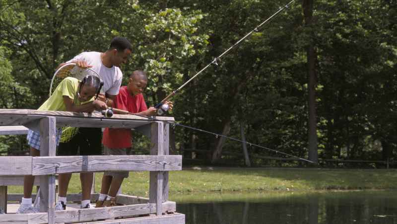family-fishing-from-a-bridge-at-a-local-pond