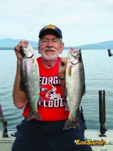 Gene Rush holds up the pair of handsome rainbow trout he caught while slow trolling worms at Lake Almanor on July 8.