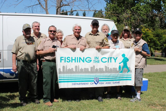 Joe Ferreira (center) and CDFW staff and volunteers for the Fishing in the City pose in front of the program's van