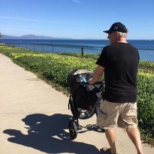 man pushing stroller in california