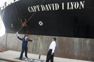Capt. Dana Lyon, the widow of Capt. David Lyon, swings a champagne bottle to christen the ship named for her late husband on Aug. 11, 2014.