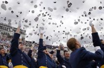 Air Force Academy graduates throw their caps into the air as F-16 jets from the Thunderbirds make a flyover May 28 at the U.S. Air Force Academy, in Colorado Springs, Colo.  (Brennan Linsley/AP)