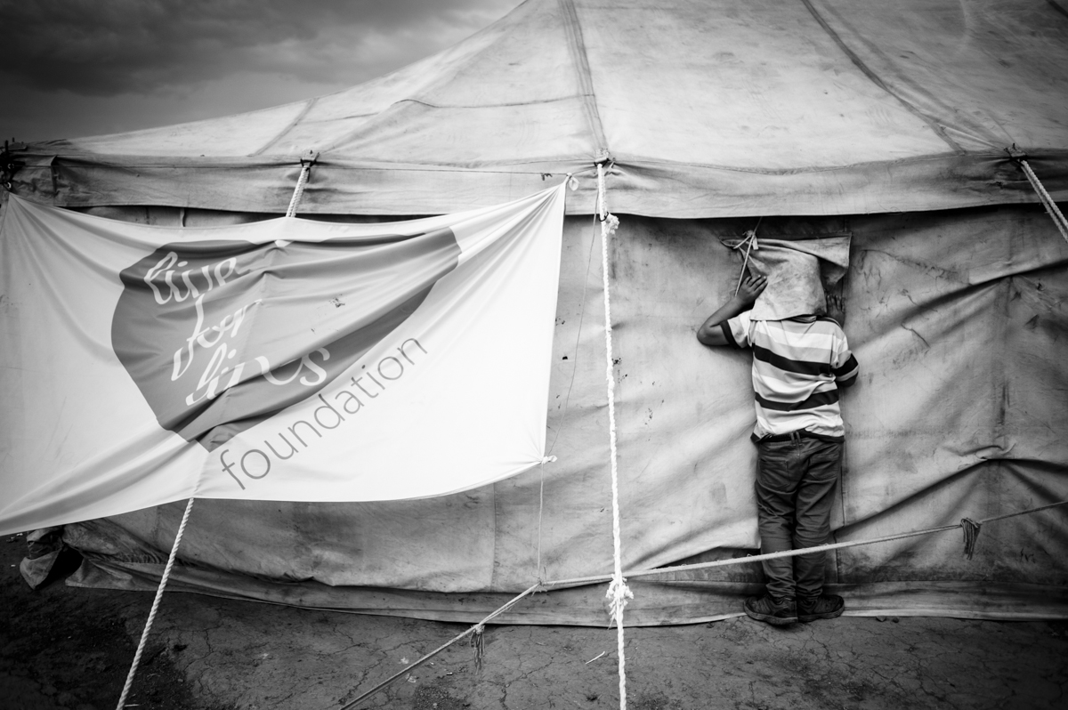 idomeni - Greece april2016 - kid looking inside a volunteers tent at the main camp