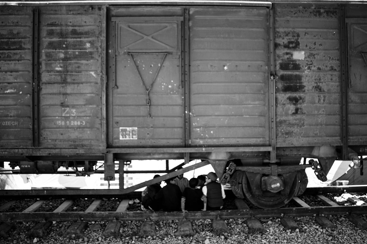 Idomeni - Greece april 2016 -kids chatting sitting on the main railway, under a train vagon