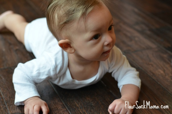 baby crawling on wooden floor
