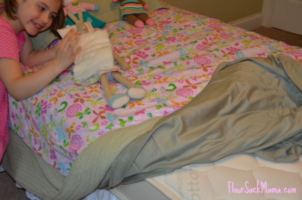 Child playing with bunny doll on bed - organic cotton mattress showing