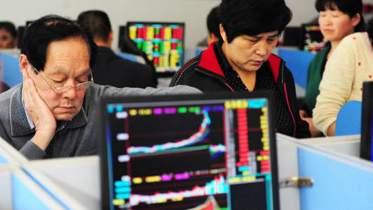 Investors watch computer screens at a stock exchange hall on May 8, 2015, in Fuyang, China.