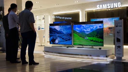 Visitors look at Samsung Electronics Co. SUHD televisions