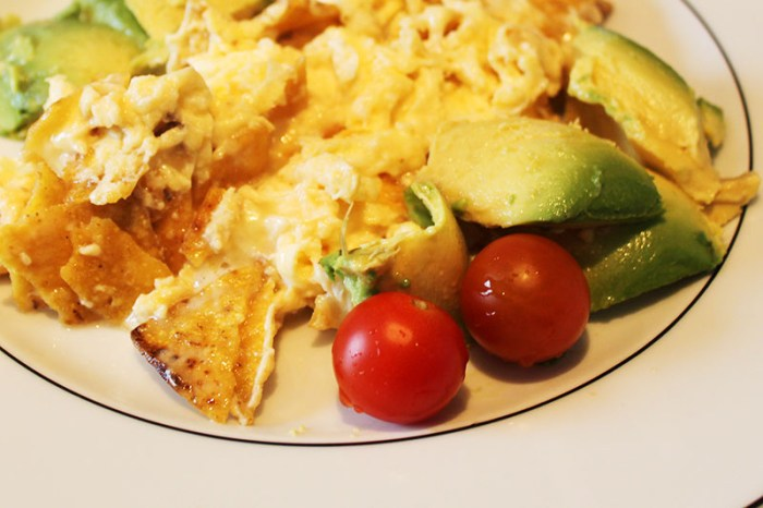 scrambles eggs with tortillas and avocado on plate