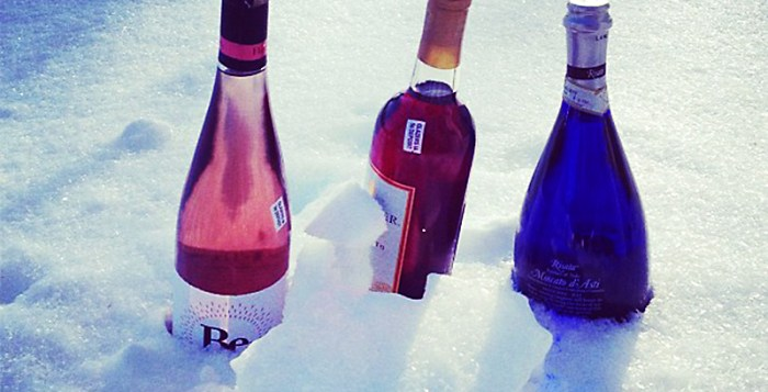 three wine bottles in the snow being chilled.