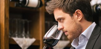 man sniffing red wine