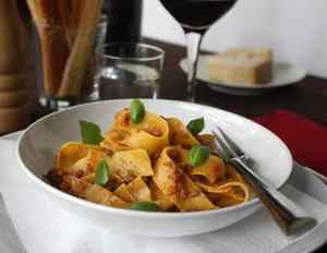 Cooked Pappardelle with an Authentic Bolognese Sauce and Fresh Basil Leaves