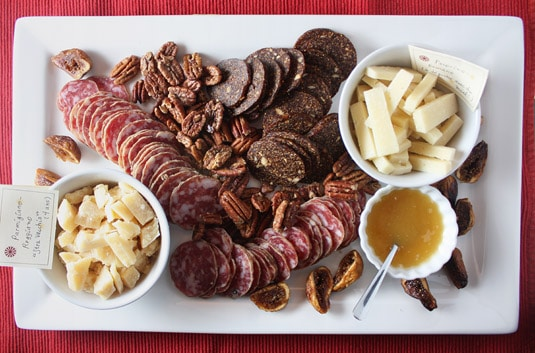 A delicious antipasti platter featuring extra-old parmigiano-reggiano, fennel-scented salami, fig &quot;salami&quot; (figs pressed with spices and nuts), crunchy spicy &amp; sweet pecans, pecorino-romano with honey and oven-roasted figs.