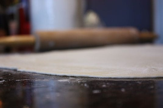 Rolling out the pizza dough 1/4-inch thick.