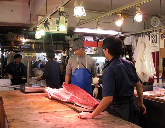 Three men getting ready to cut a 7-lb. fillet out of a huge piece of red tuna, at Tokyo's Tsukiji Market.