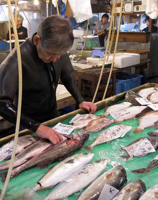 A man tending his booth. The guy is still wearing a wet suit. Yes, really. At Tokyo's Tsukiji Fish Market.