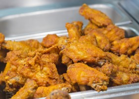 Crispy fried chicken legs and wings in restaurant tray