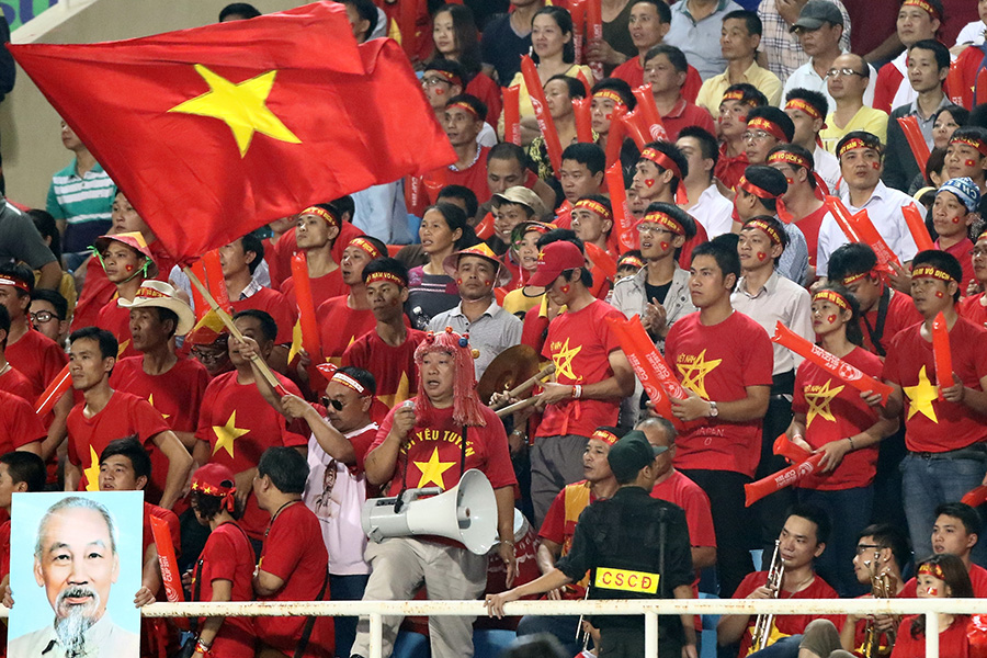 HANOI, VIETNAM - NOVEMBER 25: Vietnamese fans cheer during the 2014 AFF Suzuki Cup Group A match between Laos and Vietnam at the My Dinh Stadium on November 25, 2014 in Hanoi, Vietnam.  (Photo by Stanley Chou/Getty Images)