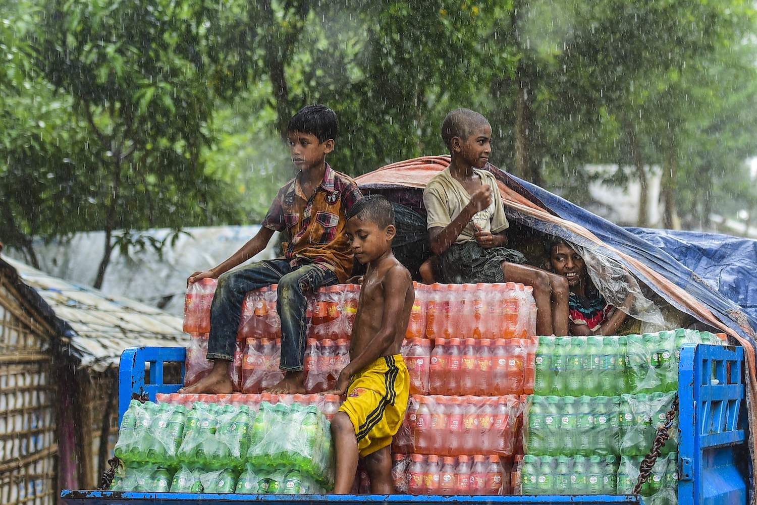 Rohingya refugee children take a ride on the back of a truck loaded with drinks during a monsoon rainfall at Kutupalong refugee camp in Ukhia on July 23, 2019.