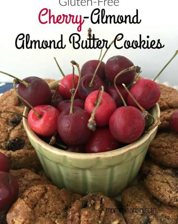A bowl full of fresh cherries with stems surrounded by fresh baked cherry almond cookies
