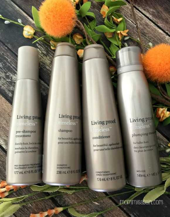 4 bottles of the Living Proof Timeless Collection for aging hair laying on table with orange flowers