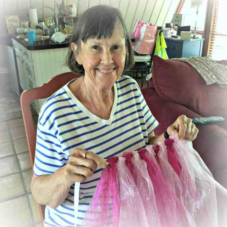 Lady holding pink tutu in her hands while other person ties the tulle around ribbon