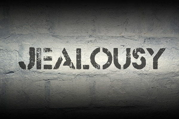 jealousy stencil print on the grunge white brick wall