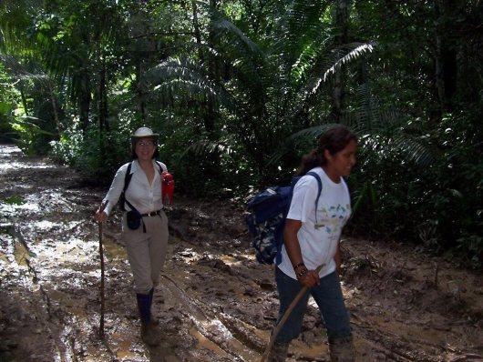 Jean follows Sonja along muddy Amazon pathway