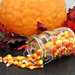 Candy corn spilling from an old mason jar onto a table that is decorated for fall.